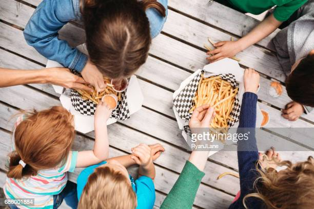friends eating at food truck - fries imagens e fotografias de stock