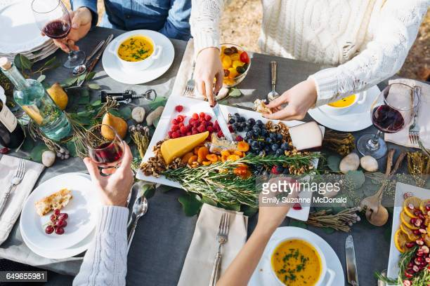 friends eating at outdoor table - farm to table stock photos and pictures