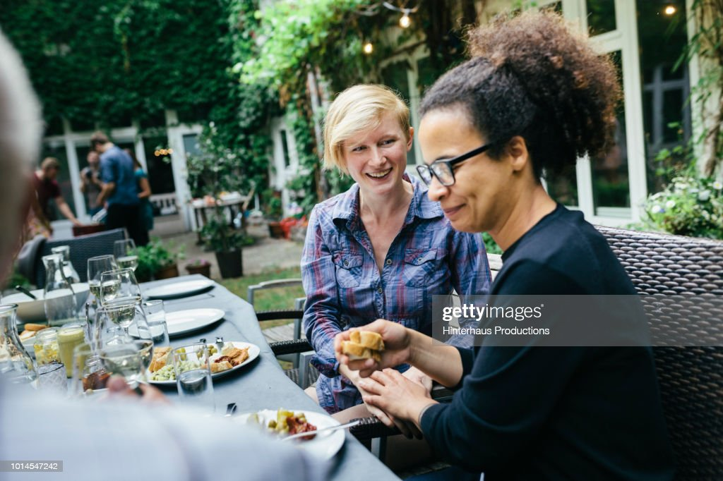 Friends Eating At Table During BBQ With Family : Stock Photo