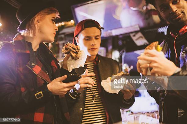 friends eating burgers in the pub - izusek stock pictures, royalty-free photos & images