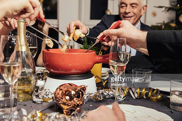 Friends eating cheese fondue on New Years Eve