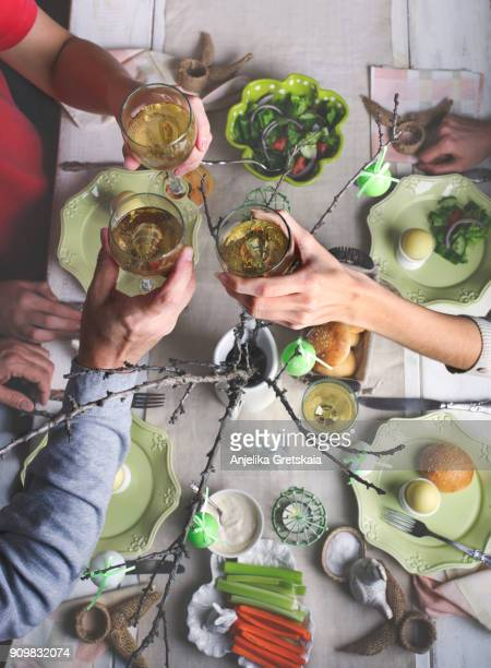 friends eating easter dinner, sitting together beside table - easter stock pictures, royalty-free photos & images