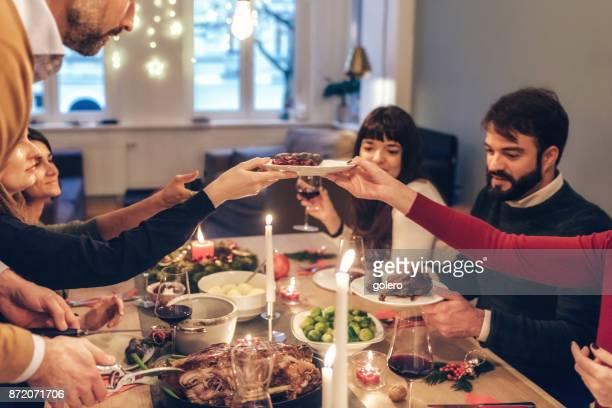 Freunde, die festliche Mahlzeit am Weihnachtstisch