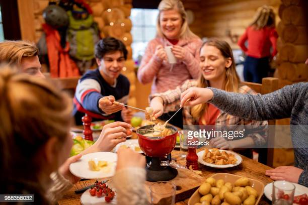 friends eating fondue at dinner - apres ski stock pictures, royalty-free photos & images