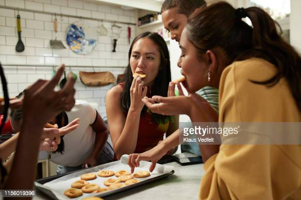 friends eating fresh cookies in kitchen at home - female friendship stock pictures, royalty-free photos & images