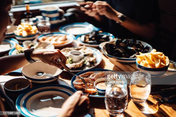 friends eating fresh seafood in restaurant - celebration stock pictures, royalty-free photos & images