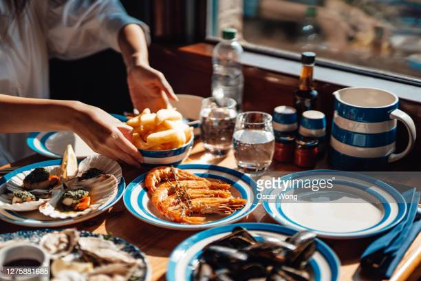 friends eating fresh seafood in restaurant - lifestyles stock pictures, royalty-free photos & images