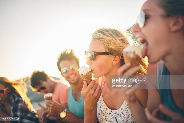Friends eating icecream on beach