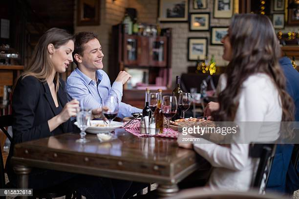 Friends eating italian food in restaurant
