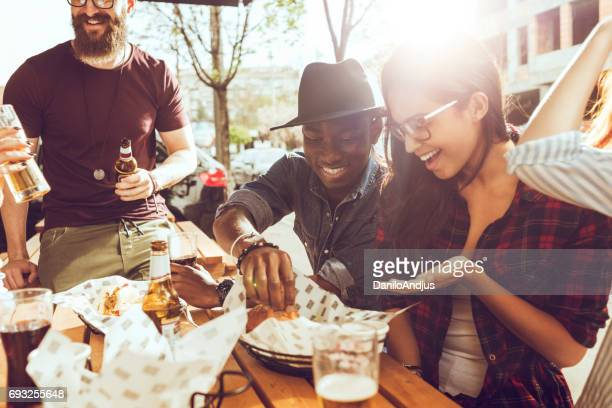 friends eating outdoors on a picnic - man eating woman out stock photos and pictures