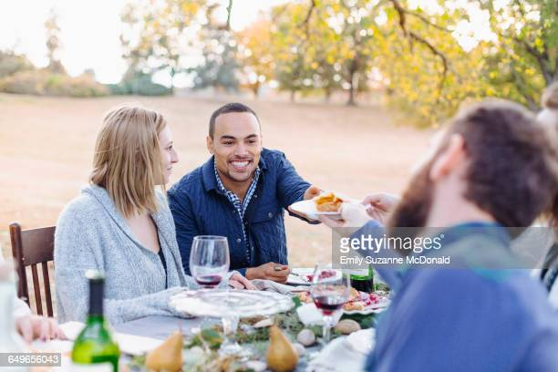 Friends eating pie at outdoor table