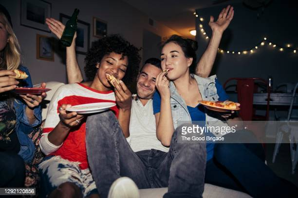 friends eating pizza on sofa during party at home - diversity stock pictures, royalty-free photos & images