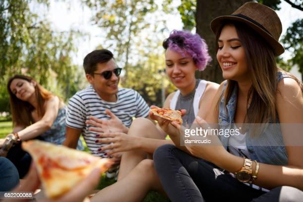 Amigos comer pizza fuera de