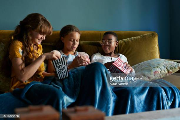 3 friends eating popcorn together, at home - blue film video stock pictures, royalty-free photos & images