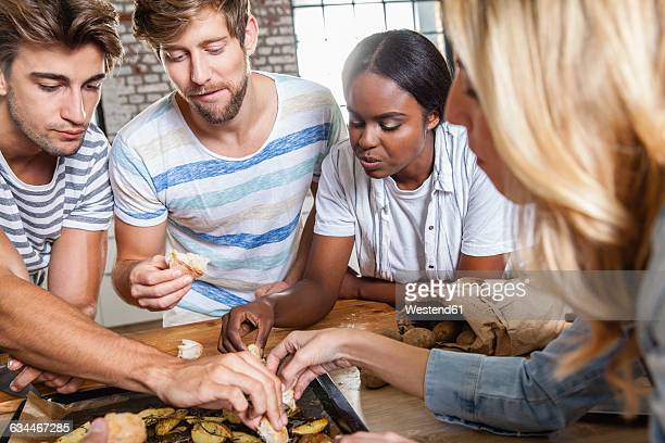 Friends eating potato wedges from baking tray