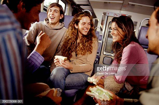 Friends eating sandwiches on train