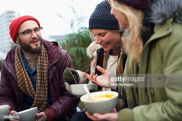 Friends eating soup in urban roof garden.