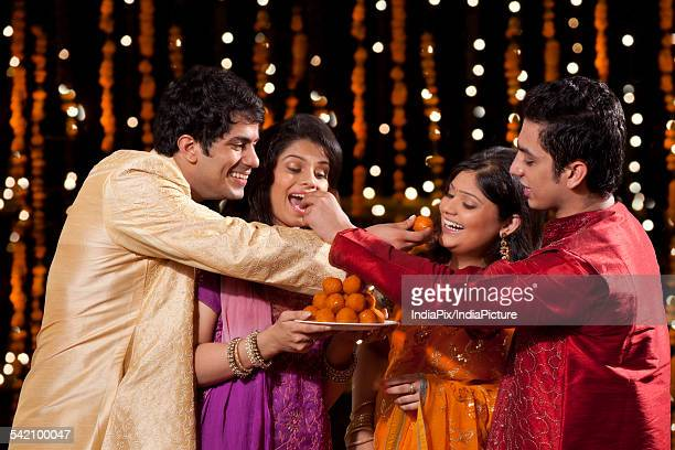 friends eating sweets - mithai stock pictures, royalty-free photos & images