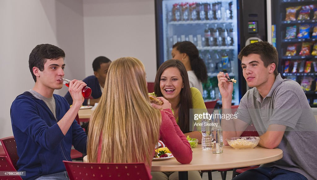 Friends eating together in lunchroom : Stock Photo