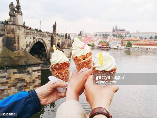 friends eating trdelnik with ice cream with view over charles bridge, prague, czech republic - prag stock-fotos und bilder