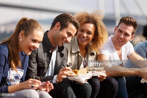 Friends eating turkish baked potato near Bosphorus bridge in Ist