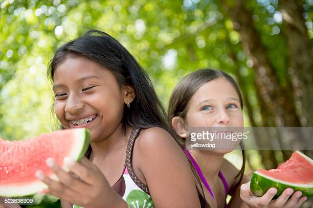 Friends eating watermelon in garden