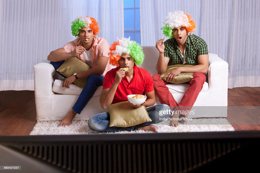 Friends eating while watching tv : Stock Photo