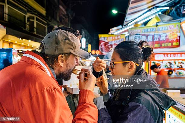 friends eating with chopsticks asian night market - non western script stock pictures, royalty-free photos & images