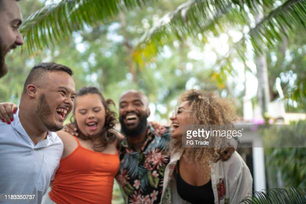 friends embracing and singing together during family reunion - persons with disabilities stock pictures, royalty-free photos & images