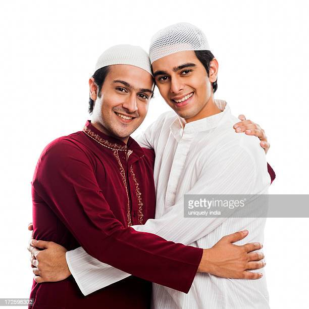 friends embracing each other during eid festival - eid al adha stock pictures, royalty-free photos & images