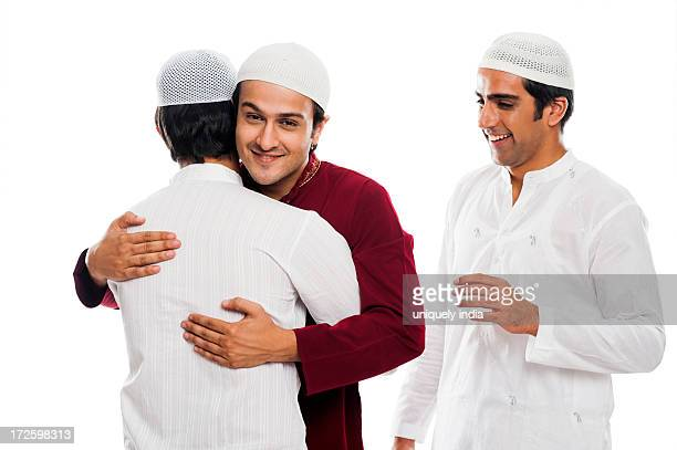 friends embracing each other during eid festival - eid mubarak photos et images de collection