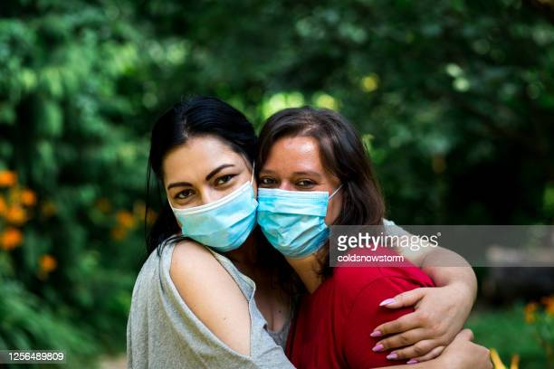 friends embracing outdoors wearing protective face masks - infectious disease stock pictures, royalty-free photos & images