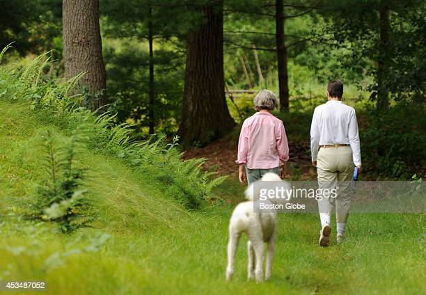 Friends Emily Hutcheson left and Laurie Bent right take a stroll in the woods near Hutcheson's Weston home on July 12 2013 along with Bent's dog...