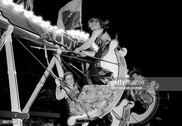 Friends enjoy a high old time in fairground swing boats in the Fellows' Garden during the Magdalene College May Ball, Cambridge, 17th June 2009....