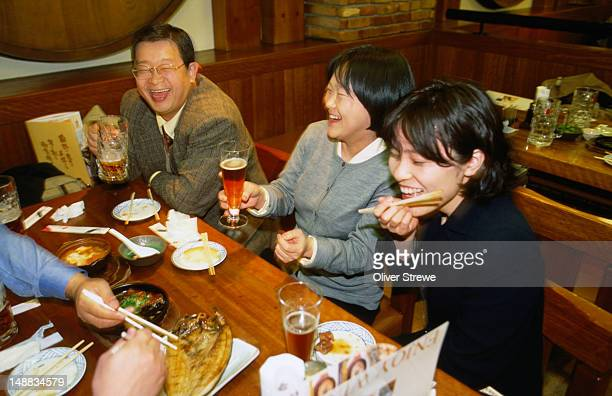 Friends enjoy a meal and a drink at a Kyoto izakaya. An Izakaya is a kind of Japanese snack bar which offers, beers and sake, and many quickly prepared homemade dishes.