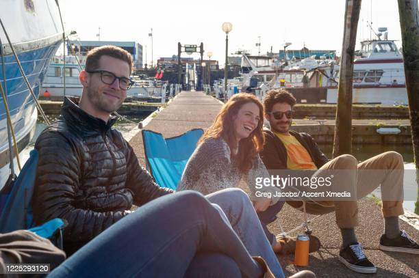 friends enjoy beverages on a boat dock - moored stock pictures, royalty-free photos & images