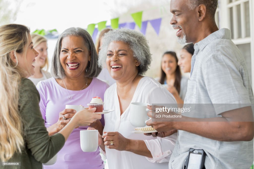 Friends enjoy coffee and cake at fundraising event : Stock Photo