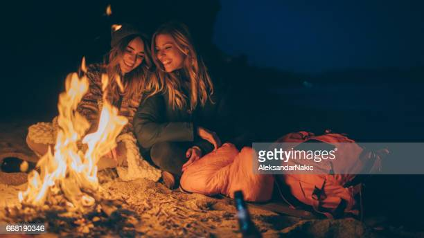 Friends enjoy evening on the beach by the log fire