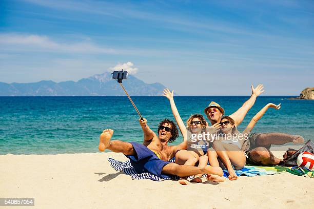 Friends enjoy holidays on Greek beach in Aegean sea