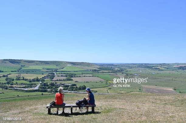 Friends enjoy the view from the top of Mount Caburn, a prominent high point on the South Downs east of Lewes in southern England on May 31, 2020 on...