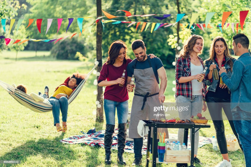 Friends enjoying a barbecue among nature : Stock Photo