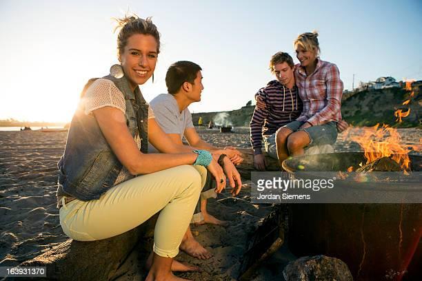 Friends enjoying a beach bonfire.