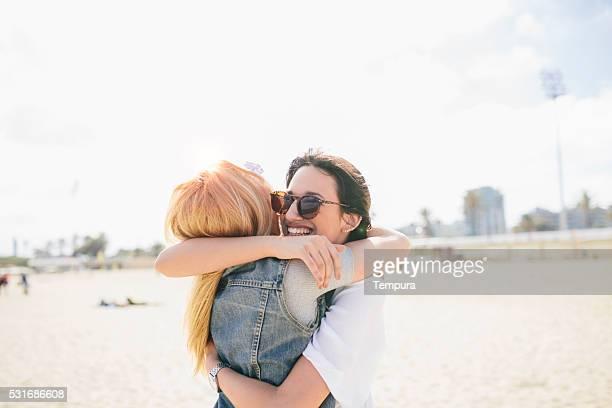 Friends enjoying a big hug in the beach.