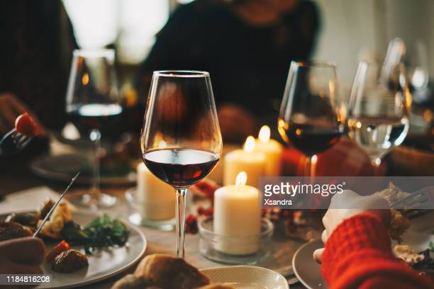 friends enjoying a christmas dinner together - evening meal stock pictures, royalty-free photos & images