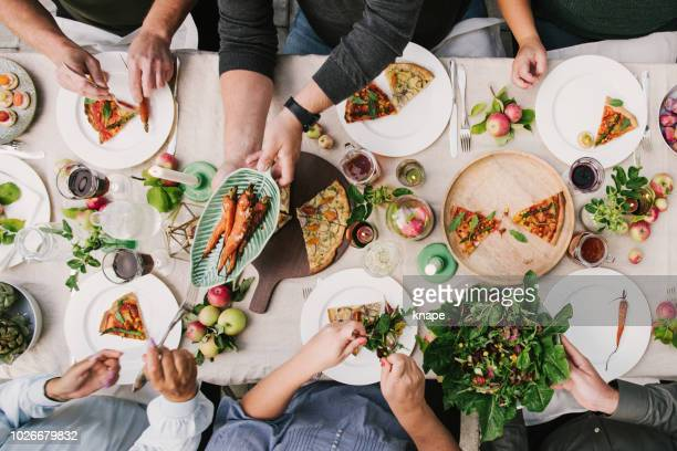 friends enjoying a dinner together in greenhouse harvest party - vegetarian food stock pictures, royalty-free photos & images