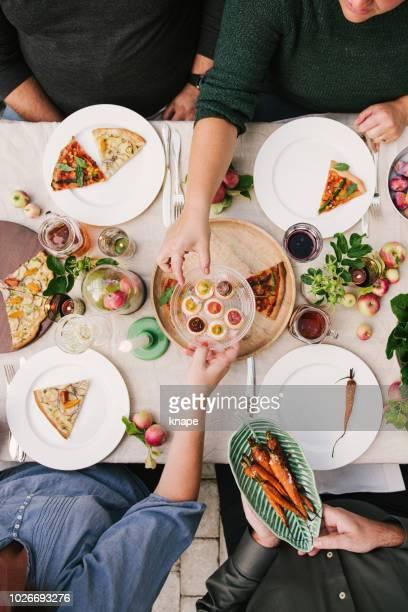 partij van de oogst van de vrienden genieten van een diner samen in kas - portie stockfoto's en -beelden