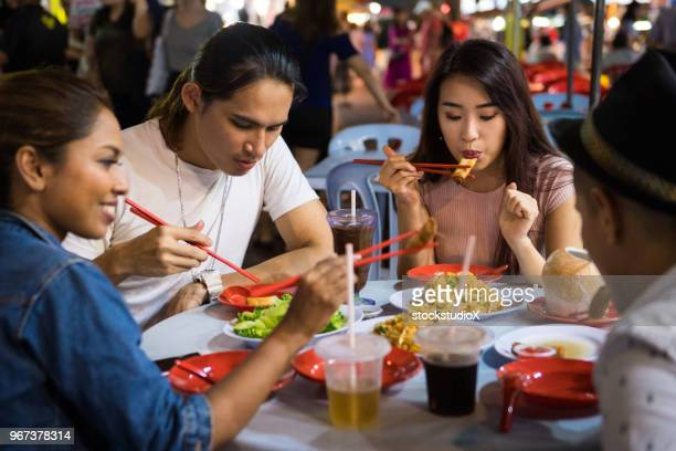 friends enjoying a local night market - malaysian culture stock pictures, royalty-free photos & images