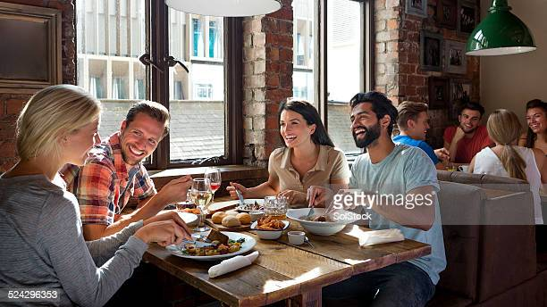 friends enjoying a meal - restaurant stock photos and pictures