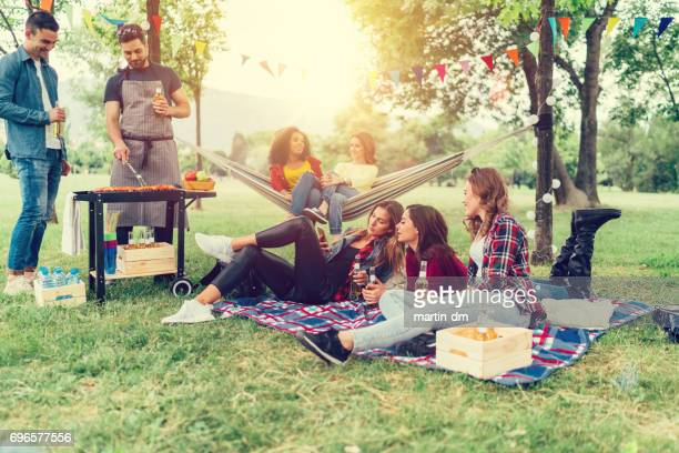 Freunde genießen ein Picknick mit Grillen im park