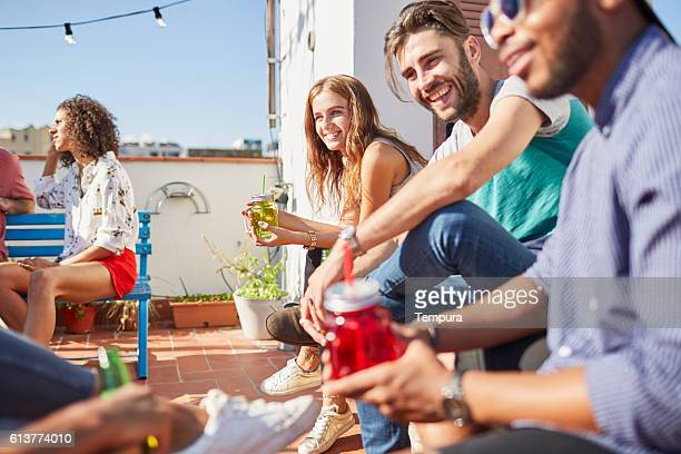 Friends enjoying a roof party in a bright suny day